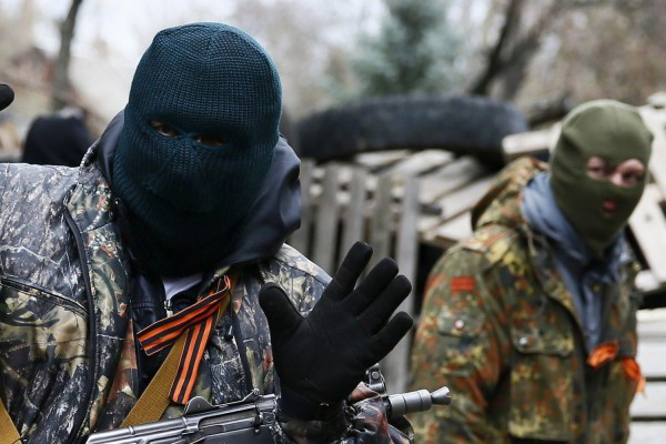 An armed man gestures in front of the police headquarters in Slaviansk, April 12, 2014. At least 20 armed militants wearing mismatched camouflage outfits took over the police and security services headquarters in the eastern city of Slaviansk seizing hundreds of handguns. REUTERS/Gleb Garanich (UKRAINE - Tags: POLITICS CIVIL UNREST)
